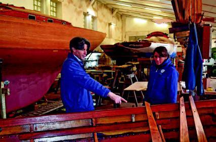Philipp Schaich und eine Mitarbeiterin in einer der Winterlagerhallen, in denen über 30 Holzyachten gewartet werden.