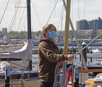 Bootsbauer mit sogenannten Alltagsmasken beim Mastsetzen.